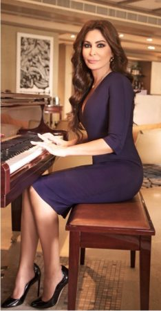 In one of her 2017 photograph sessions, Elissa wears a blue dress designed Victoria Beckham and earrings and black pumps by Dior.